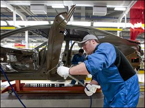 An assembly line employee works on a 2015 Chrysler 200 at the Sterling Heights Assembly Plant in Sterling Heights, Mich. The rough winter weather might have contributed to a big increase in spring automobile sales, one economist said, as weather-damaged cars were replaced or repaired.
