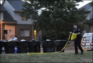 A Detroit police officer takes down the crime scene tape at the scen