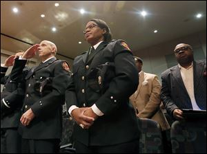 Toledo Fire Department firefighters, from left, Christopher Burns, Joseph Mazur, and  Lolita Cooper stand during their promotion ceremony.