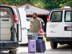 Robert Cole,  who lives at the home on South Crissey Road, holds a dog ready to be crated by the Toledo Area Humane Society.