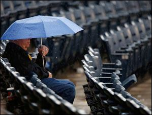 Sylvania resident John Brenner uses an umbrella to shield himself from the rain.