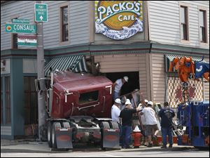 Workers remove a window from Tony Packo's Cafe on Front Street in East Toledo.