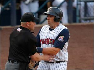 Mud Hen third baseman Mike Hessman runs into the home plate umpire after crossing the plate to score against Norfolk.
