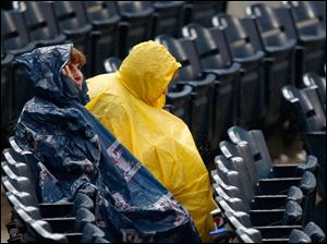 Michigan residents Kathy Burke, left, and her sister Nancy Burke wear plastic rain gear to shield themselves from the weather during a brief rain delay Thursday  night.