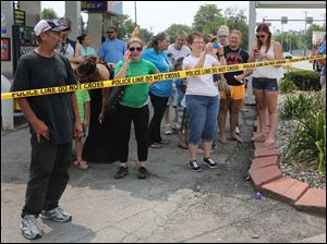 People watch as crews remove a semi truck that crashed into Tony Packo's.