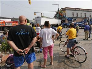 Spectators watch as workers remove a semi-trailer truck that crashed into Tony Packo's Cafe on Front Street in East Toledo.