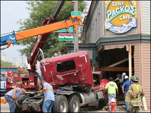 Crews remove a semi truck that crashed into Tony Packo's.