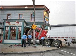 Toledo police examine a tractor-trailer after it crashed into the Tony Packo's restaurant.