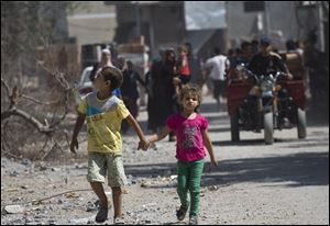 Palestinian children walk hand in hand as residents return to the heavily bombed Gaza City neighborhood of Shijaiyah today.