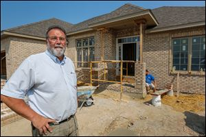 Chuck Barchick, front, stands in front of 7514 Pinafore Lane in Maumee as Sean Mowery works on the Barchick Custom home. Mr. Barchick, also head of the Home Builders Association of Greater Toledo, says his company has four homes under construction.