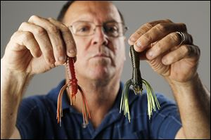 Greg Dorris holds two of his patented bass baits, called Whiskers.
