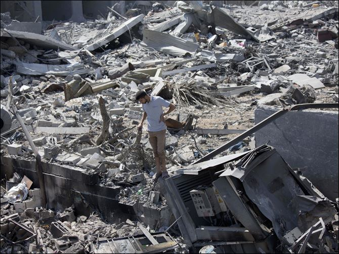 Mideast Israel Palestinians A Palestinian inspects a destroyed house in the heavily bombed Gaza City neighborhood of Shijaiyah, close to the Israeli border, today.