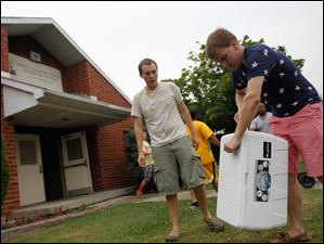 Aidan Hubbell, 19, left, a BGSU sophomore, and Peter Funk, 20, right, a BGSU sophomore carry out a cooler that was full of water at the Martin Luther King Center Kitchen for the Poor.