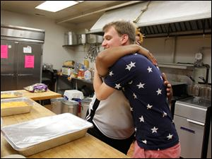 Head Cook Henrietta Armstrong, left, hugs Peter Funk, 20, a BGSU sophomore, right, for the water he and his friends brought to the Martin Luther King Center Kitchen for the Poor