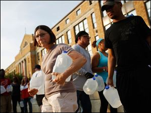 Kathy Wielfaert, left, of West Toledo, walks away with two two gallon jugs of water in her arms at Central Catholic High School.
