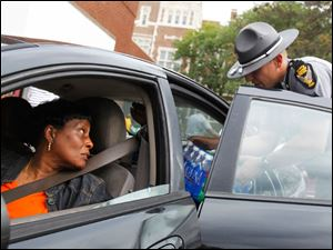 Jefferson, left, of South Toledo, looks back as officer Kohl Man, right, loads a case of bottled water into her car at Waite High School.