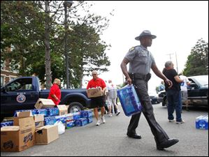 Sargent Chris Fitzgerald, center, and other police officers and volunteers load water into citizens' cars at Waite High School.