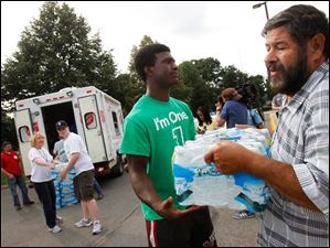 Simeon Washington, left, 15, a junior at Central Catholic High School hands water to Osama Dudar, right, of East Toledo from a Salvation Army van full of bottled water from the American Red Cross at Central Catholic High School.