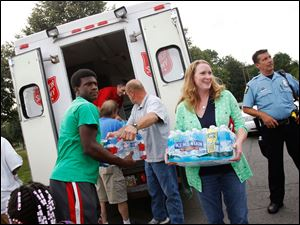 Volunteers unload a Salvation Army van full of bottled water from the American Red Cross at Central Catholic High School.