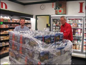 Michael Kazmaier (left), manager of Kazmaier's, helped navigate the pallet to the front of the store. Assisting him was Bill Schramm.
