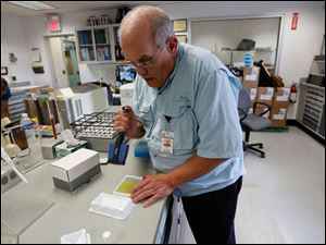 Jeff Martin, senior chemist, at the Toledo Waster Treatment plant, tests 13 water samples for microcystin.