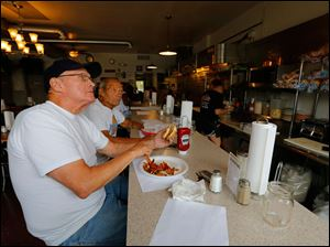Brothers Butch, left, and Denny Varnes, Toledo, watch news coverage of the water crisis as they grab a bite to eat at My House Diner on Lewis Avenue. The diner was serving food on paper plates so they didn't have to wash dishes.