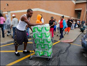 Donald White hauls off water he purchased at Walgreens, 4580 Monroe Street.