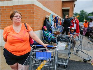 Holly Tipping, Toledo, is at the front of the line  as she waits to pick up water she purchased at Walgreens, 4580 Monroe Street.