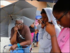 Mary Guy, left, Toledo, and her nieces Hope Gonzales and Tamara Woodard, right, wait on line to pick up water they purchased at Walgreens, 4580 Monroe Street.