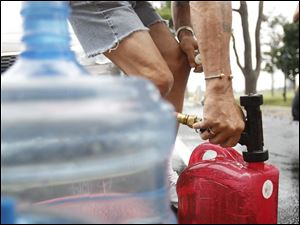 William Hart of Point Place fills up a jug with water at an Oregon fire station.