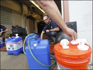 Firefighters Bryan West, left, and Tom Phillips, right, fill up various containers with water at the fire station at the fire station at 1102 S. Wheeling St. in Oregon.
