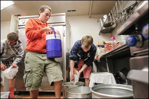Tynan Hubbell, 14, left, of St. John's High School, and BGSU students Aidan Hubbell-Staeble, 19, center, and Peter Funk, 20, pour out water from various containers at the Martin Luther King Center Kitchen for the Poor.