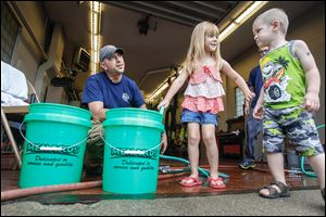 Clara Cousino, 4, center, and Clay Cousino, 2, right, both of East Toledo help firefighter Bryan West fill buckets at the fire station in Oregon.