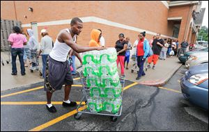 Donald White hauls off water he purchased at Walgreens on Monroe Street on Saturday.