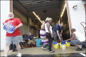 Firefighters and citizens work to fill containers with water at the fire station at 1102 S. Wheeling St. in Oregon.