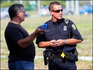 Dan Rogers, left,  President & CEO Cherry Street Mission Ministries, and TPD Officer Joseph Taylor, right, discuss how to redirect the public to water distribution areas after the supplies offered by the Cherry Street Mission, at the former Macomber High School, were gone by mid-morning.