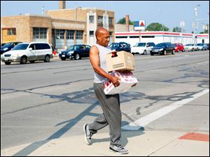 Melvin Newton, from Toledo, carries containers of water across Monroe Street that he got at the water distribution center sponsored by the Cherry Street Mission on August 3, 2014. The line of cars behind, which was waiting for water, was backed-up all the way to Dorr Street.