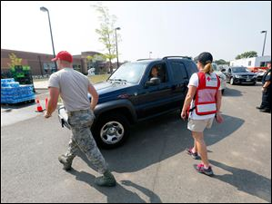 Shelly Genaro, with the American Red Cross, directs traffic to a water distribution area for free water at Woodward High School.