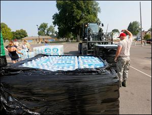 Staff Sgt. Josh Reiss, of the 200th Red Horse Engineers, directs a pallet of water to a storing area in the parking lot of Woodward High School.