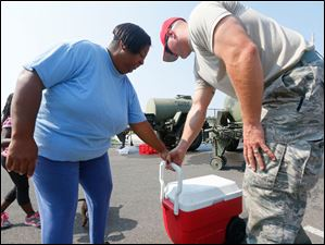 Suzette Moore, left. from Toledo, accepts a cooler filled with purified drinking water from Staff Sgt. Brock Mowry, right, of the 200th Red Horse Engineers,  at Woodward High School. Moore waled to the distribution center with her family to get potable water.