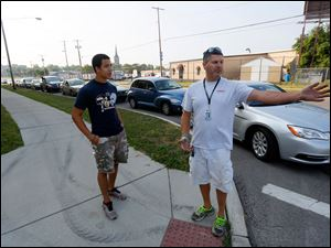 Volunteer Noah Rose, left, 16, and Shawn  Kellerbauer, right, an employee with the Cherry Street Mission, direct traffic along Washington and 16th Streets to the area at the former Macomber High School building where people were able to get free water until supplies ran out.