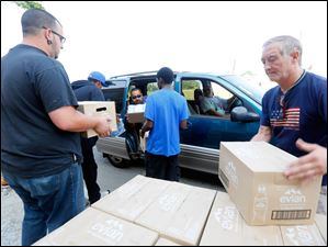 Volunteers including Carl Schellkopf, right, help load free water into cars for the public at a water distribution area at the former Macomber High School.