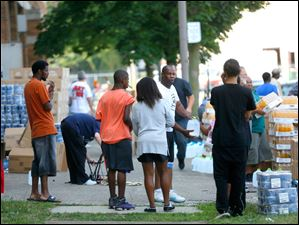 Willie Knighten Jr., center in white shirt, hands out jugs of free water to a family who walked to the former Macomber High School building to get clean drinking water.