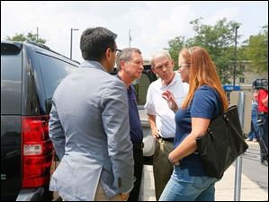 Ohio Gov. John Kasich, left, Senator Randy Gardner (R), center, and State Representative Barbara Sears, right, have words before Gov. Kasich leaves after a closed door meeting with Mayor D. Michael Collins and other dignitaries to address the water emergency in Toledo.