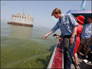 Collin O'Mara, president of the National Wildlife Federation, points out algae blooms near the Toledo water intake crib in Lake Erie.