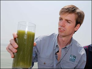 Collin O'Mara, president of the National Wildlife Federation, holds a glass of algae filled Lake Erie Water, taken from the lake near the Toledo water intake crib.