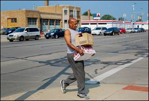 Melvin Newton of Toledo carries cases he received at the water distribution center sponsored by the Cherry Street Mission.