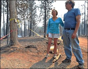 Nancy and Victor Rineman of Phoenix, Ore. stand in front of the entrance to their destroyed 20-acre summer retreat where five cabins once stood in the area of the Soda Mountain Wilderness in Oregon