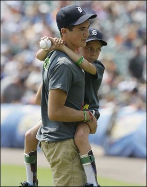 Braden Gandee, 7, held by his brother Hunter is seen after tossing out the ceremonial first pitch before an interleague baseball game between the Detroit Tigers and the Colorado Rockies on Sunday in Detroit.