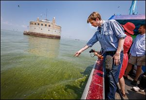 Collin O'Mara, president and CEO of the National Wildlife Federation, points out algae blooms near the Toledo water intake crib in Lake Erie. The algae bloom season is just beginning.